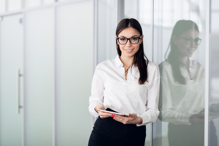 Young business woman with tablet computer opening glass office door