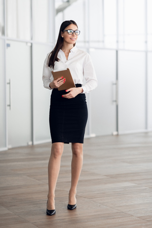 Business woman wearing white blouse standing in office hall with tablet computer and smiling. 写真素材
