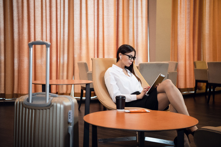 Businesswoman sitting at the airport bussiness lounge, waiting for the flight. Smiling woman wearing glasses sitting on sofa at airport waiting area. 免版税图像