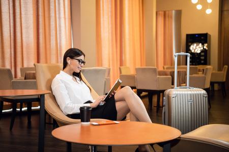 Zelfverzekerde zakenvrouw die muziek luistert op haar tabletcomputer terwijl ze in een stoel zit in de businesslounge op de luchthaven