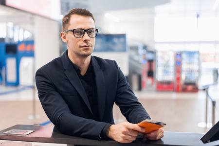 Business trip. Handsome young businessman in suit holding his passport and talking to woman at airline check in counter in the airport Фото со стока