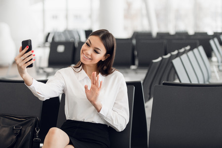 Traveler businesswoman with smartphone, waving hand for greeting in front camera during video call, waiting in lobby hall at airport. Woman passenger traveling abroad on business trip. Air flight concept