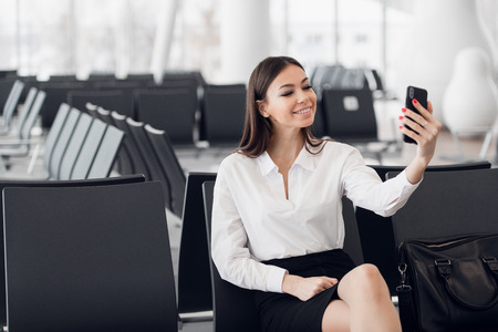 Young business woman at international airport, making selfie with mobile phone and waiting for her flight. Female passenger at departure terminal, indoors.