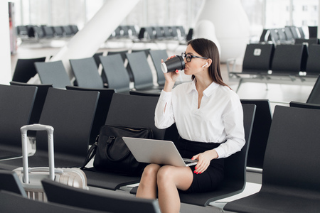 Young businesswoman in the airport, using laptop and drinking coffee, travel, business trip and active lifestyle concept