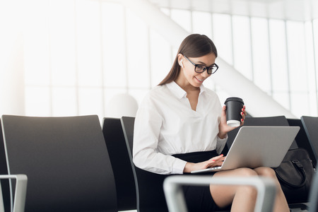 Woman enjoys laptop and drinks coffee at airport terminal