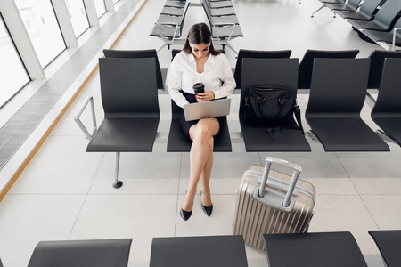 Casual woman working on laptop in airport hall. Woman waiting his flight at airport terminal, sitting on chair and typing on the laptop.