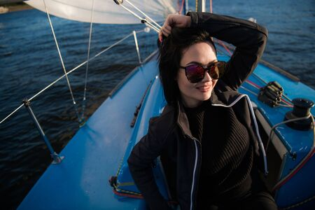 Beautiful young woman sits on yacht bowl and poses. She wears sunglusses with hand and smile. Model is sailing on board of yacht. 写真素材