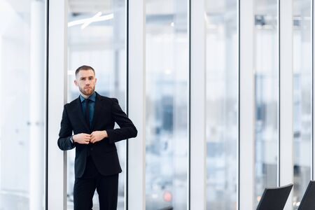 Stylish young businessman wearing a modern suit, who is a high achiever, standing on the top floor of an office building looking out at the view through large windows