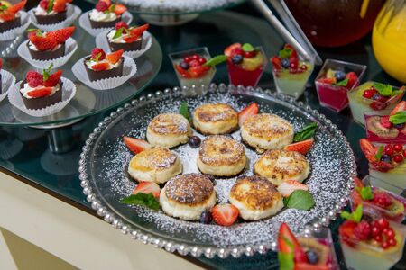 Cheesecakes with sour cream, mint, strawberries on a breakfast buffet