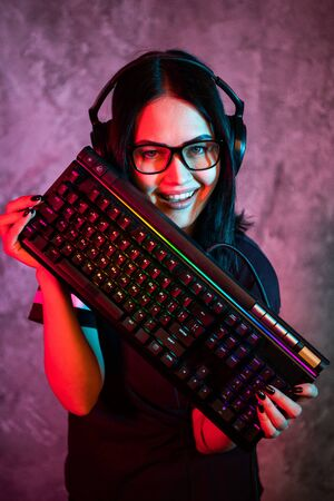 Funny nerd girl wearing glasses carrying computer keyboard Stockfoto