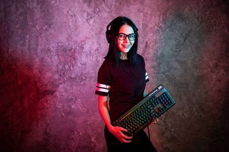 Funny nerd girl wearing glasses carrying computer keyboard Banco de Imagens - 129638306