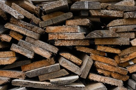 Folded old wooden brown and gray planks in a sawmill. Piled alder boards as texture. Stockfoto