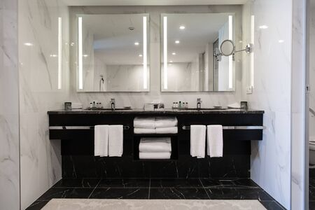 Modern twin bathroom with sinks, mirrors and towels