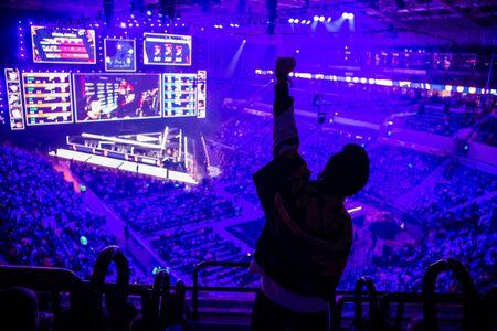 Grand événement esport. Fan de jeux vidéo sur une tribune à l'arène des tournois avec les mains levées. Bravo à son équipe favorite. Banque d'images