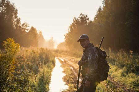 Bird Hunter at Sunrise going for hunt in a forest with his shotgun rifle.