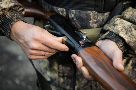 Nahaufnahme eines Jägers, der seine Schrotflinte lädt Standard-Bild