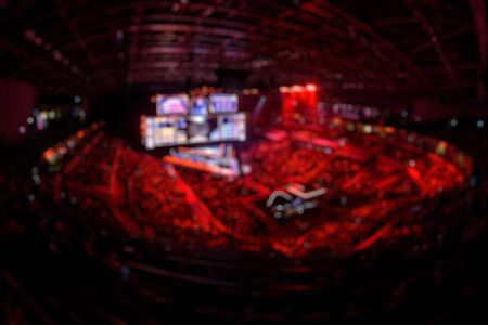 Blurred background of an esports event - Big illuminated main stage of a computer games tournament located on a big stadium. Tribunes are full of video games fans.