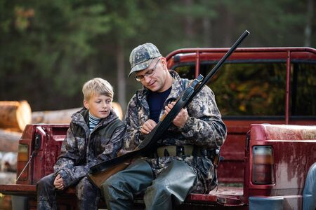 Father and son sitting in a pickup truck after hunting in forest. Dad showing boy mechanism of a shotgun rifle.