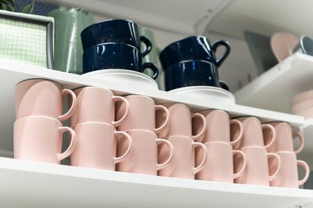 Mugs on shelf on a shelf in retail gift store. Pink and dark blue coffee mugs on shelf in kitchen. Stack of ceramic cups on shelf, stack of clean ceramic coffee cups in coffee shop.