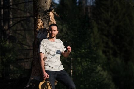 fine art portrait of a hipster man wearing sunglasses in a forest. Archivio Fotografico