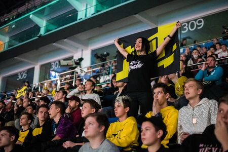 MOSCOW, RUSSIA - OCTOBER 27 2018: EPICENTER Counter Strike: Global Offensive esports event. Happy girl fan on a tribune at arena with team Natus Vincere flag. Cheering for her favorite team. Editoriali