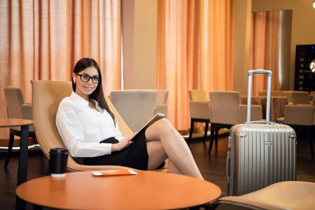 Businesswoman sitting at the airport bussiness lounge, waiting for the flight. Smiling woman wearing glasses sitting on sofa at airport waiting area. Archivio Fotografico