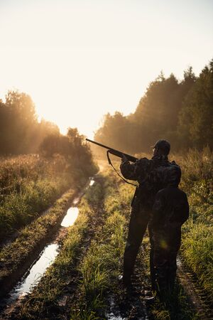 Hunters with hunting equipment going away through rural field towards forest at sunset during hunting season in countryside.