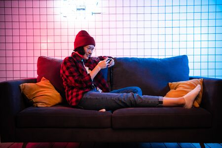 Close up portrait of pretty teenager girl playing online game in telephone wearing casual jeans denim shirt outfit clothes sitting on cosy sofa Banco de Imagens