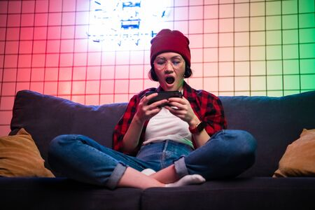 Closeup portrait of pretty young woman looking shocked, open mouth and eyes, cell phone playing online mobile game, watching sports match or reading an sms, e-mail, viewing latest news