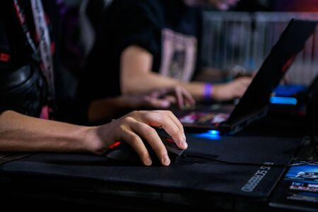 MOSCOW - DECEMBER 23 2019: esports Counter-Strike: Global Offensive event. Close up of hand over Game Mouse at gaming event. Gamer playing on a laptop. 新闻类图片