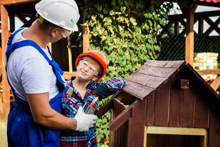 Père et fils travaillant ensemble dans un atelier en bois. Ils se concentrent sur la construction d'une niche en bois, le fils est assis à l'intérieur avec un pinceau. Prêt à peindre la maison. Banque d'images
