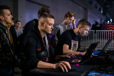 MOSCOW - DECEMBER 23 2019: esports Counter-Strike: Global Offensive event. Ex-professional gamer Denis siezed Kostin playing on a laptop with a fan at special fan zone at gaming event. 新闻类图片