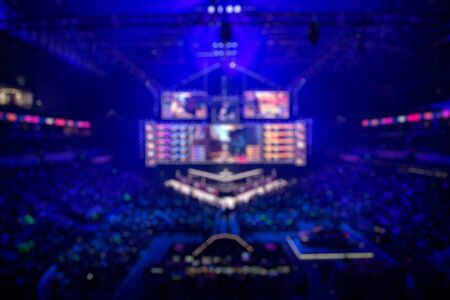 Blurred background of an esports event - Main stage venue, big screen and lights before the start of the tournament.