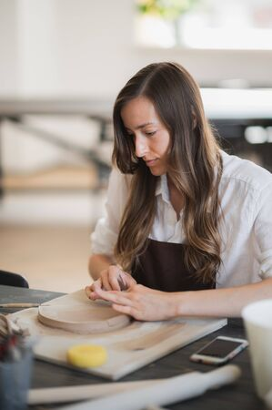 Womans fingers adding and adjusting a clay part on a future ceramic product. Imagens