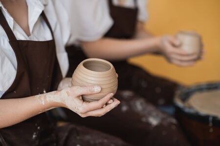 The female potters finished making a clay vase remove it from the potters wheel. Creating vase of white clay. Making ceramic products from white clay, closeup Reklamní fotografie