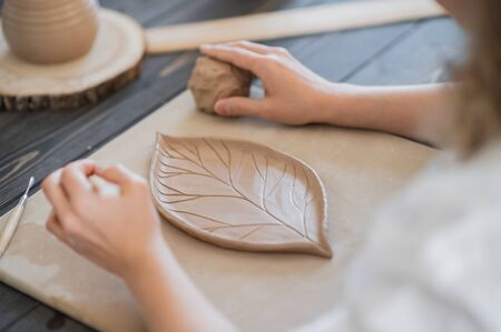Woman decorating handmade pottery plate close-up