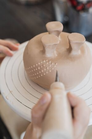Child in the process of decorating the clay vase. Children pottery studio.