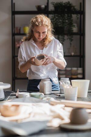 Female potter glazing raw unburned ceramic cup using brush. Earthenware mug putting colorant on pottery workshop.