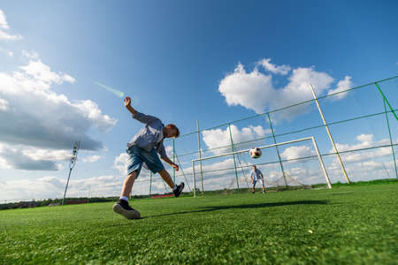 Boy kicking a penalty at goal. Low angle wide view.