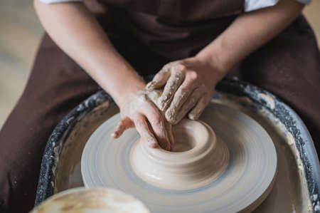 Close-up view of woman hands working on pottery wheel and making clay pot. Hands sculpts a cup from clay pot. Workshop on modeling on the potters wheel