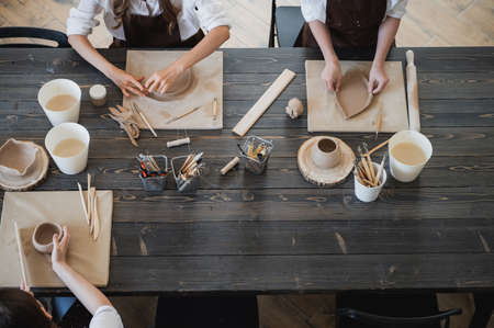 Top view of female hands sculpting different clay products. Big wooden table with pottery tools on a workshop.