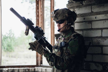 Brutal military man is sitting and cleaning and preparing his gun to the battle.