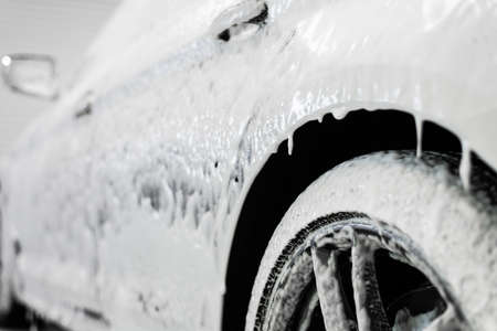 Car washing process. Foaming detergent covers side of the car, clean it from dirt and dust.