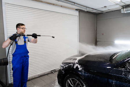 Worker cleaning automobile with high pressure water jet at car wash.