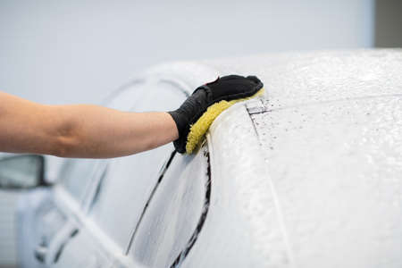 Man washing a soapy black car in a cleaning and detailing service.