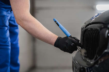 Close-up of man hand in black protective gloves cleaning radiator grille with special brush. Carwash and detailing service. 版權商用圖片