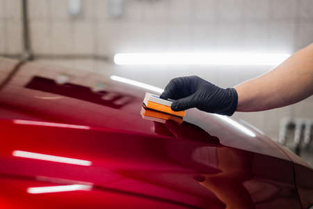 Man worker of car detailing studio applying ceramic coating on car paint with sponge applicator