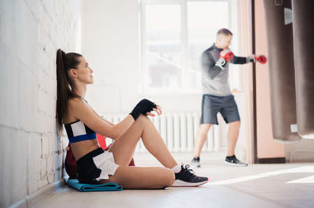 A beautiful girl with long hair is sitting on a sports mat in the gym against the background of a boxing man