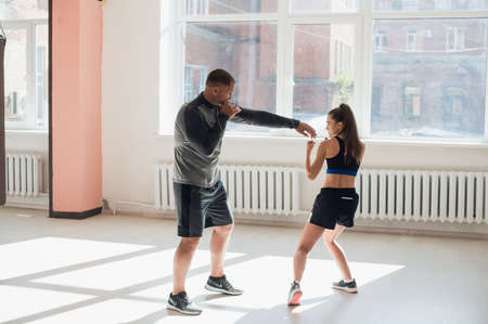 An attractive young boxer teaches his girlfriend boxing techniques in a loft equipped for boxing training