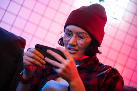 Teen girl exciting playing smart phone in a room lit with neon color at home. Standard-Bild